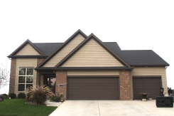Ranch style house with tan siding, tan vinyl cedar shakes, brown brick front brown garage door brown trim