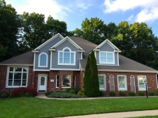 two story house with brick and fiber cement shake gables