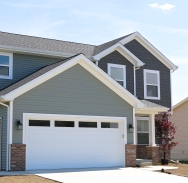 Quiet Willow green siding with dark shakes pair nicely with white trim and white garage door.