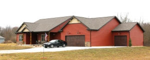 Redwood red siding, wicker tan shakes, dark roof, and wooden garage doors in East Peoria il