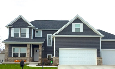 two story grey siding and grey shakes, white shutters and white garage door, tan brick.