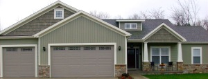 craftsman style house with vertical green siding and faux cedar shakes