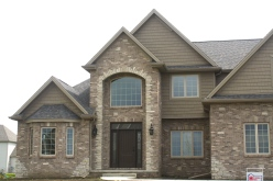 grand 2 story house with brown brick and stone accents, weathered door roof