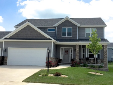 home with gray siding and darker gray shakes white trim, grey entry door and white garage door with no windows