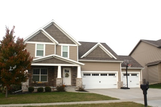 crafts man style house with shake gables separated by white band. white carriage style garage door, tan siding