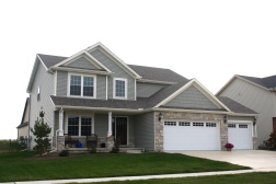 two story green house with white carriage style garage door, green shakes