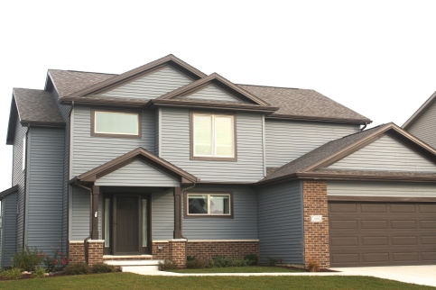 Two story house with blue siding, dark brown trim, dark brown garage door, dark brown roof
