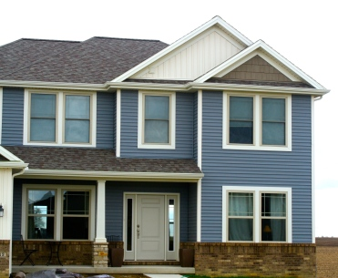 two story blue house with cream and tan accents. Faux cedar skaes