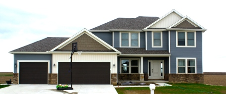 blue two story house with 2 garage brown garage doors.