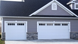 white carriage style garage doors in grey home with stone knee wall
