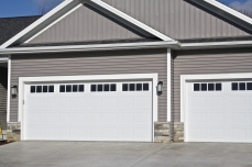 Grey house with white carriage style garage doors