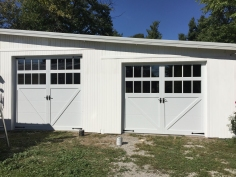 carriage style garage doors with two rows of windows and door hardware