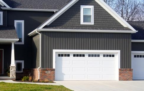 white garage doors in dark siding and red brick