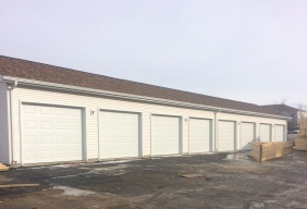 a bunch of plain white garage doors without windows