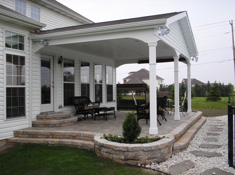 covered porch with decorative landscaping and patio furniture