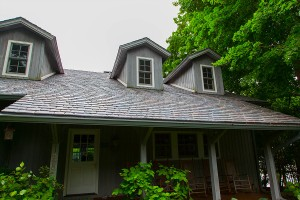 Lake wood house with wooden siding with fake slate roof