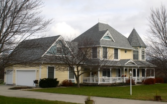 turret roof and widows walk on yellow house with grey roof and blue gables