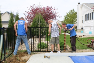 crew measuring fence panel to drill fence post