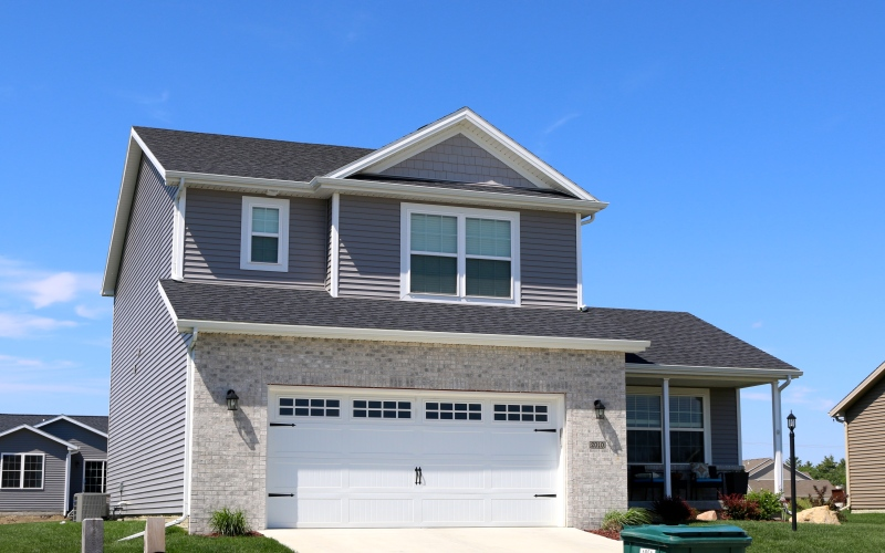 Harbor Grey siding with Victorian Grey shakes, white trim, white carriage style garage door and CertainTeed Landmark Black roof