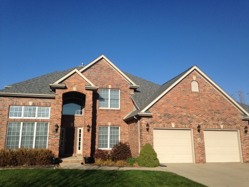 brick home with grand entrance and grey roof