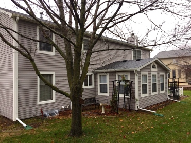 house with grey siding and white trim and wide window casings