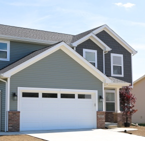 Quiet Willow Green Siding with Twilight Shadow dark shakes, white trim, white carriage style garage door with no hardware and plain windows