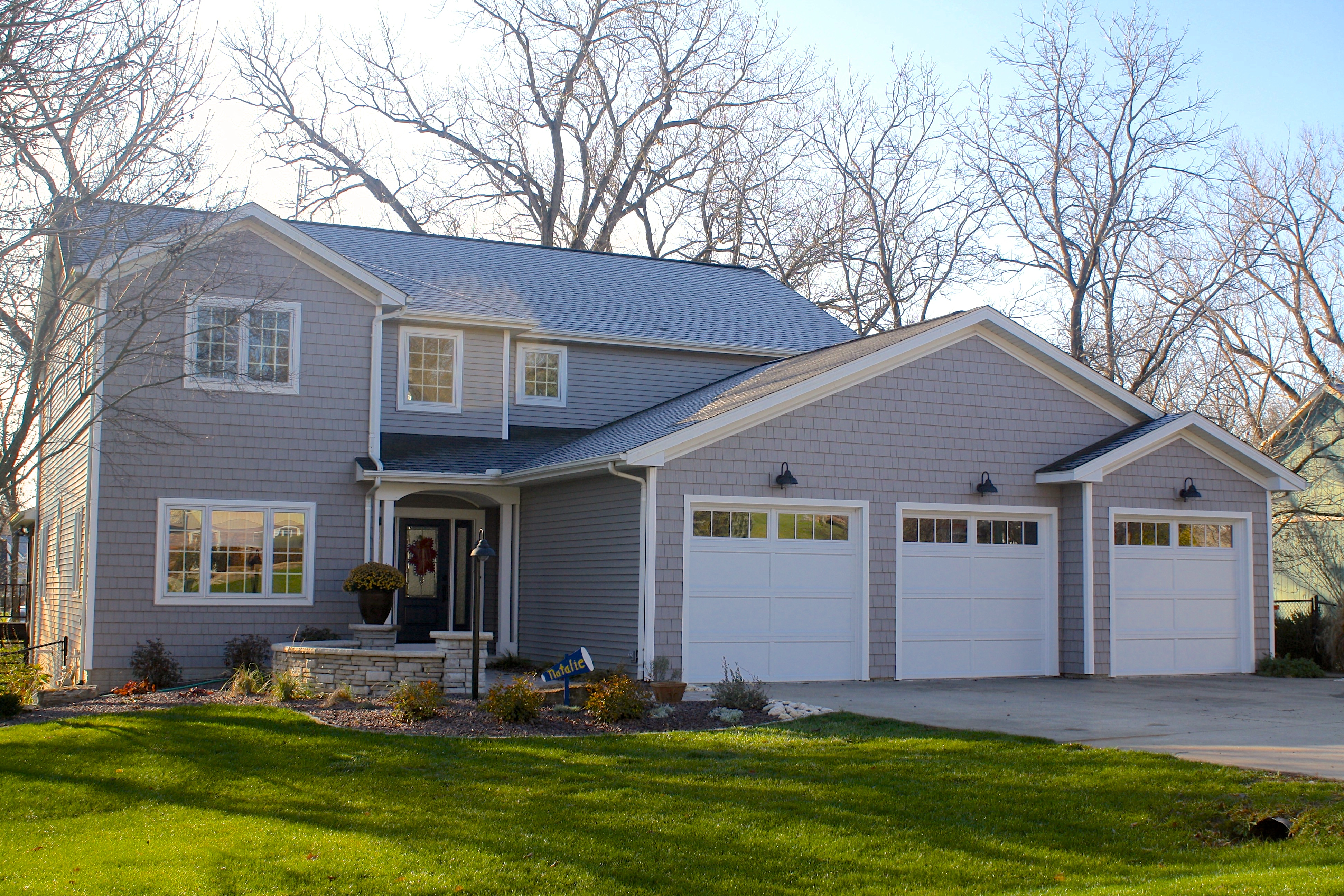 grey house with lots of grey shakes and white trim white garage doors