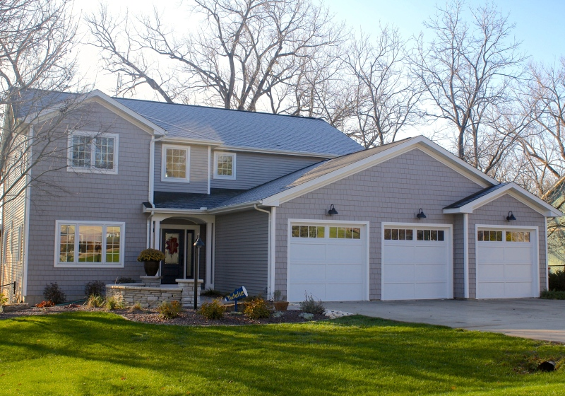 grey house with lots of grey shakes and white trim, white garage doors