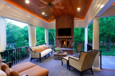 covered porch with nice patio furniture, fireplace, tv, and ceiling fan