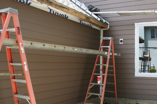 Siding panels are installed first. Corners, trim, and window casings are installed last.