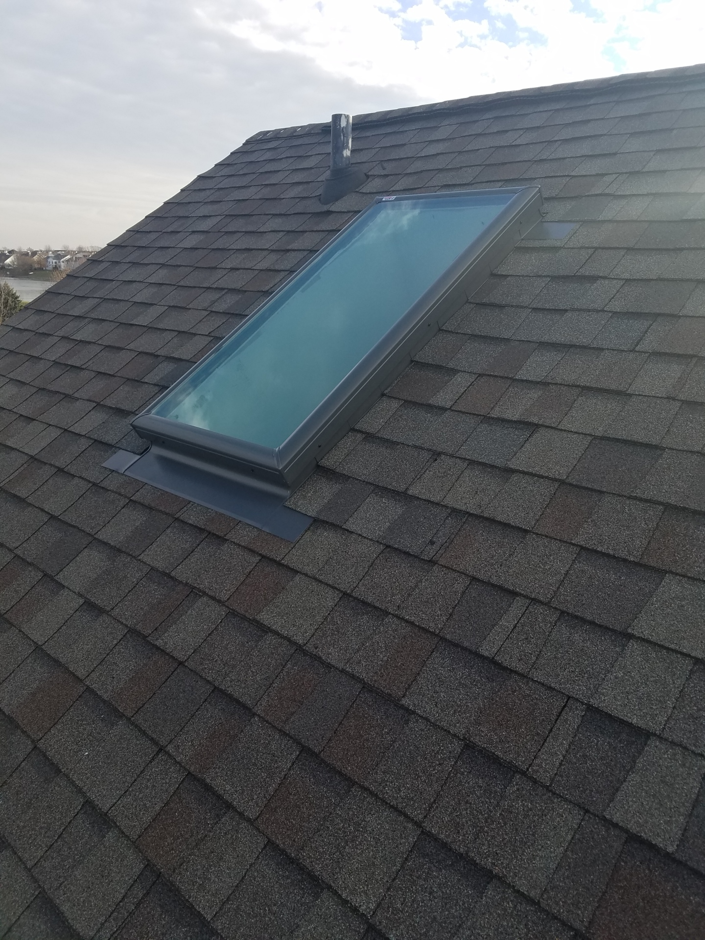 A new velux skylight installed on roof with shingles installed to match as closely as possible
