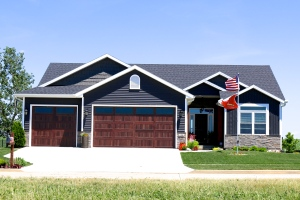Ironstone grey siding with white trim, black roof, and faux wood garage doors in normal il